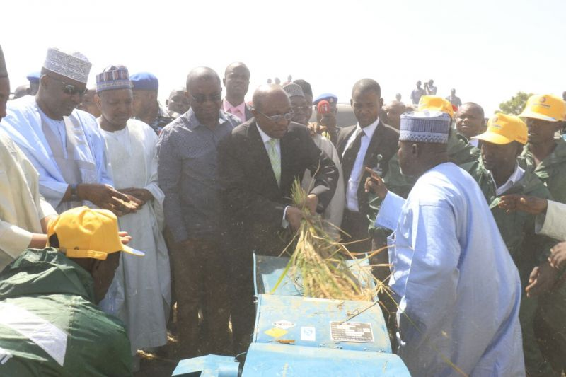 Governor, Central Bank of Nigeria, Mr Godwin Emefiele,( flanked to the left by) Acting Director, corporate communications CBN, Mr Isaac Okorafor, Kebbi state Governor, Senator Abubakar Atiku Bagudu, Jigawa state Deputy Governor, Alhaji Ibrahim Hassana, demonstrating threshing of rice in Auyo local Government Area of Jigawa State on Thursday, Nov. 10, 2016.