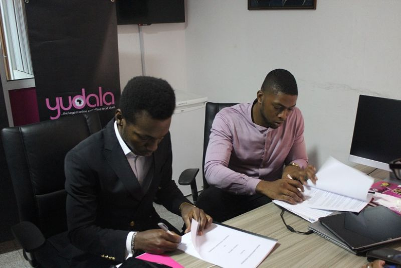 Multi award-winning Gospel artiste, Frank Edwards and Founder/Vice President, Yudala, Prince Nnamdi Ekeh signing the contract documents during the unveiling of Edwards as Yudala brand ambassador.