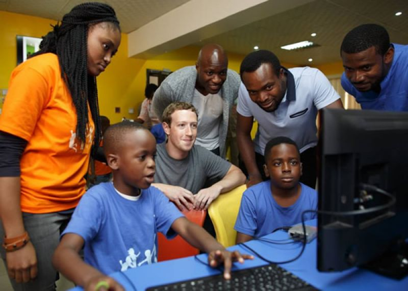Facebook CEO, Mark Zuckerberg inspecting the activities of some Nigerian kids on the computer on his first visit to Lagos, Nigeria.