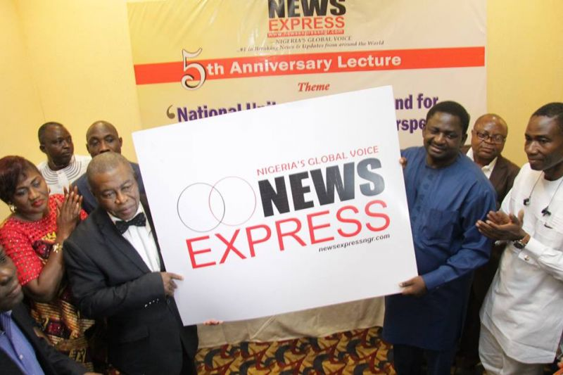 Chairman of the occasion, Chief Goddy Uwazurike (L) and Presidential Spokesman Femi Adesina displaying the new News Express logo while other dignitaries watch . . . on Thursday at Sheraton Hotel & Towers, Ikeja, Lagos.
