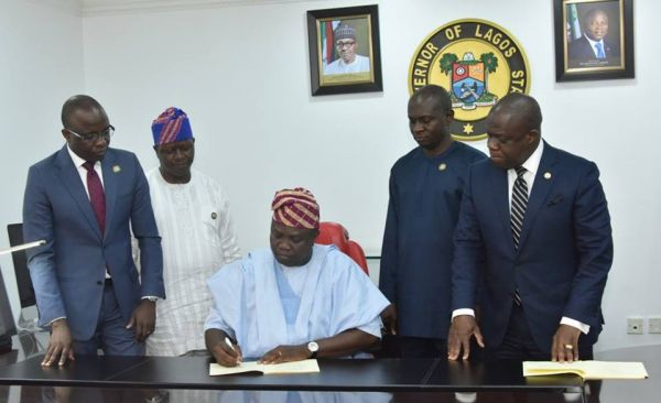 •Governor Ambode signing the bills into law on Thursday as aides watch
