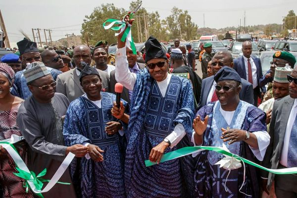 •President Buhari cutting the tape to commission a road project in Jos on Thursday
