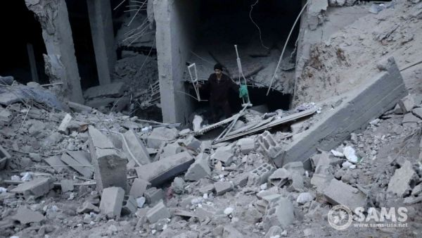 •A man walks out of a building's rubble carrying two crutches in Eastern Ghouta [Courtesy of SAM