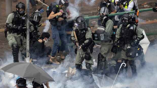 Hong Kong protesters fight off police with fire, arrows